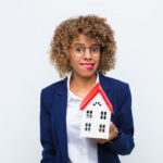 what to do with the house: puzzled woman holding model of a house