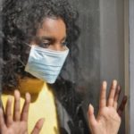 Divorce As Quarantine Ends: woman with face mask looks out window