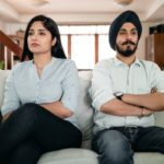 minimizing conflict: couple on couch with arms crossed
