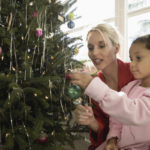 Holidays After Divorce during COVID-19: mom hangs christmas tree ornaments with daughter