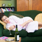 rejection phase after divorce: woman on her couch drinking & smoking in her bathrobe